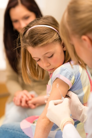 Little girl getting vaccination from pediatrician at medical office photo