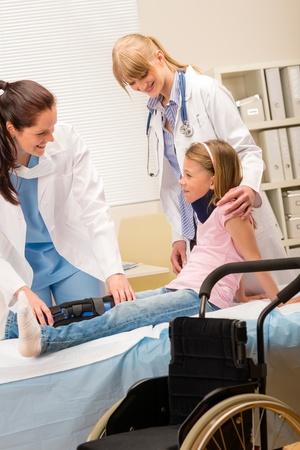 Due dottoresse esaminare rotto sedia a rotelle bambina gamba