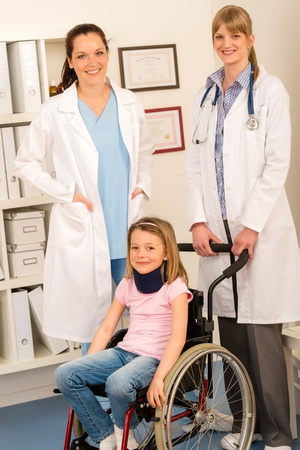 Little injured girl on wheelchair with doctors assistance photo