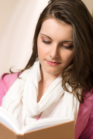 Young brunette woman reading book wear pink jumper Stock Photo - 13556240