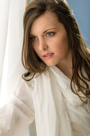 Beautiful thoughtful woman in white looking out of window Stock Photo - 13556245