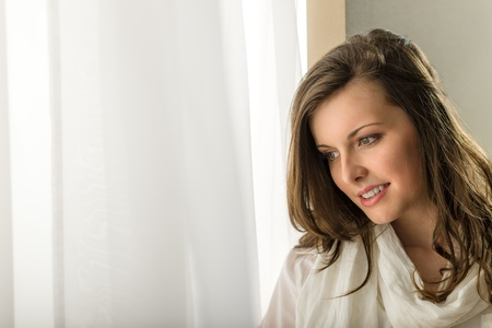 Beautiful thoughtful woman in white looking out of window Stock Photo - 13563741