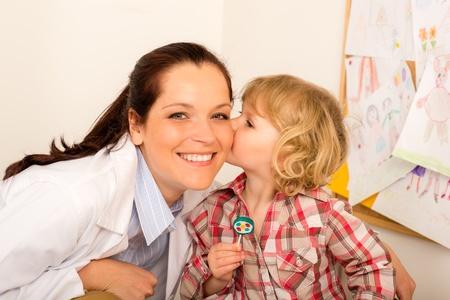 pediatrician: Thank you doctor - Little girl kissing female pediatrician Stock Photo