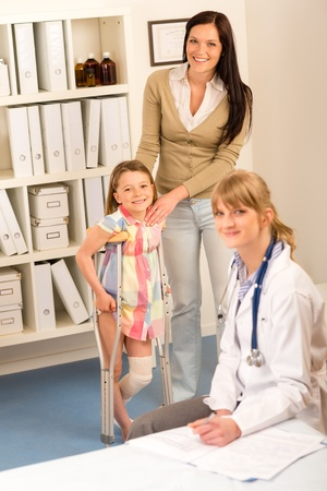 Little girl with bandaged leg standing with crutches mother assistance photo