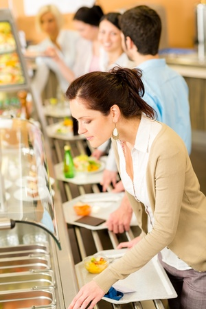 Business woman choose cafeteria lunch buffet carry serving tray photo