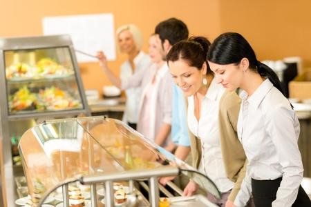 El almuerzo de oficina Cafetería dos colegas mujer a elegir postre comida de auto-servicio