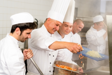 busy restaurant: Professional kitchen happy chef prepare food meal international cuisine