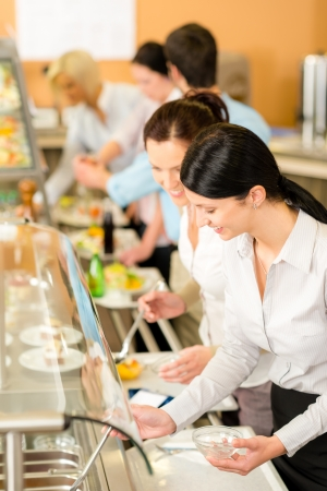 buffet lunch: Cafeteria lunch two office colleagues woman choose food dessert self-service Stock Photo