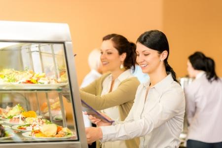 Una mujer joven tome el almuerzo cafetería cantina ensalada de placa de los alimentos frescos
