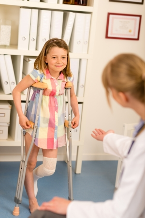 leg injury: Little girl with bandaged leg standing with crutches surgery office
