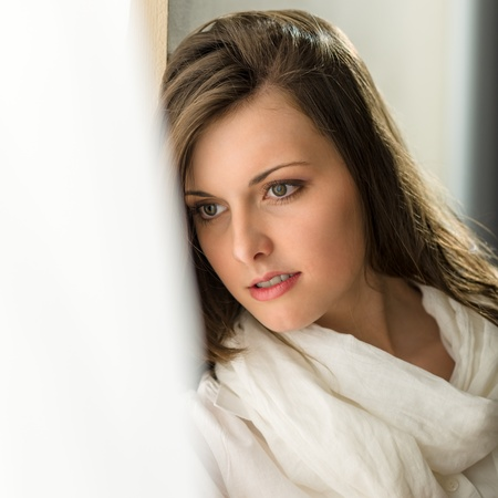 Beautiful thoughtful woman in white looking out of window Stock Photo - 13629751
