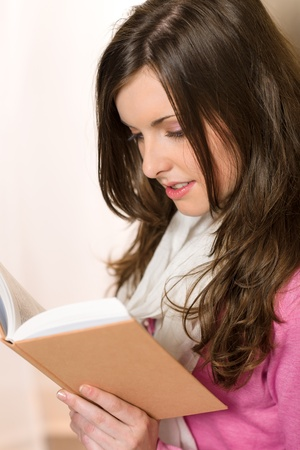 Young brunette woman reading book wear pink jumper Stock Photo - 13630934