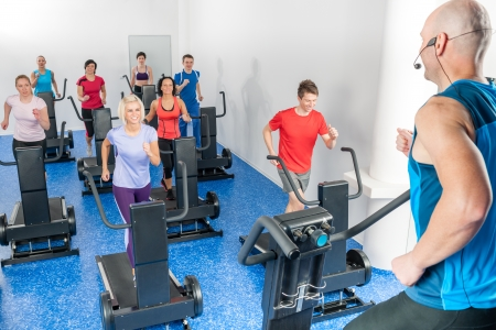 Alpinning class of young adults with fitness personal trainer photo