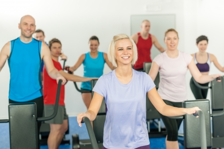 Fitness young group on treadmill running trainer at health gym photo