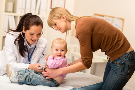 Cute baby being examine by pediatrician with stethoscope mother assistance photo