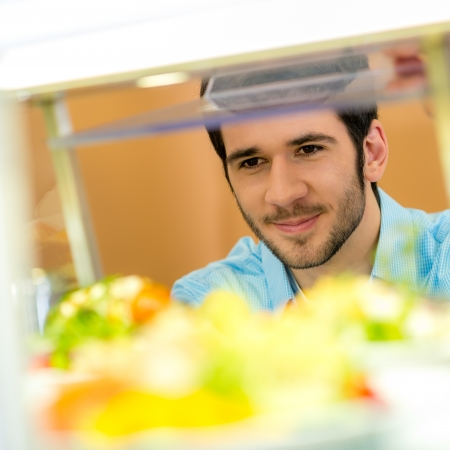 canteen: Cafeteria food display cabinet young man choose salad healthy lifestyle Stock Photo