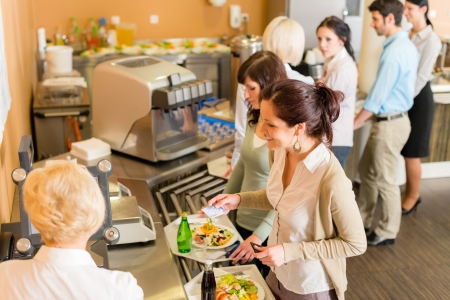 canteen: Cafeteria woman pay at cashier hold serving tray fresh food Stock Photo