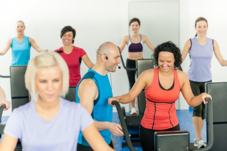 Fitness instructor leading class of alpinning at the gym photo