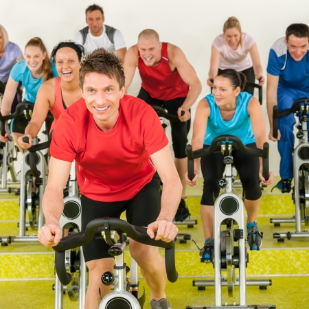 fitness instructor: Fitness instructor leading spinning class people exercise enjoy physical workout