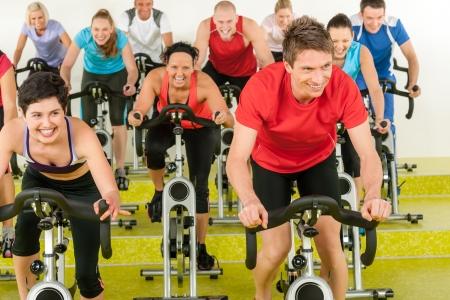 Spinning sportive gens de la classe exercice d'entraînement au gymnase profiter