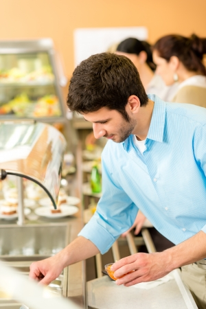 Business man take cafeteria lunch food from display cabinet self-service photo