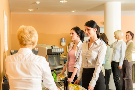 to queue: Cafeteria woman pay at cashier hold serving tray fresh food Stock Photo