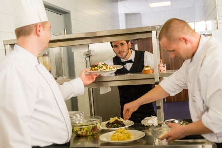 Professional kitchen cook prepare food service give meals to waiter photo