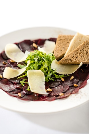 vegetarian carpaccio with beetroot, nuts and toast on white plate photo