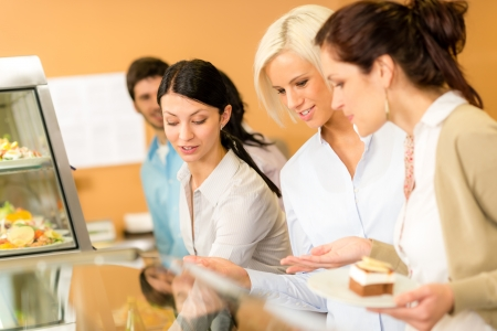 dessert buffet: Cafeteria food young woman look dessert selection at office canteen