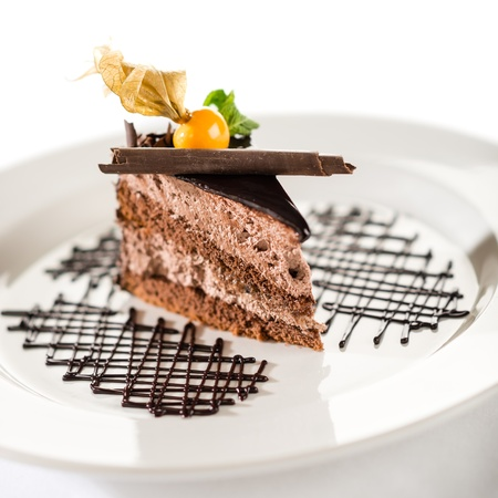 Delicious chocolate cake with physalis on white plate and isolated photo