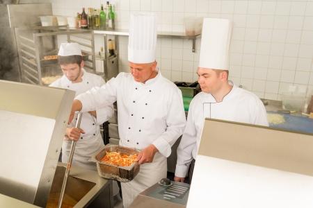 cocinas industriales: Cocinero profesional con el equipo de preparaci�n de alimentos en la cocina industrial Foto de archivo