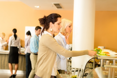 canteen: Lunch break business woman select meal from display counter canteen Stock Photo