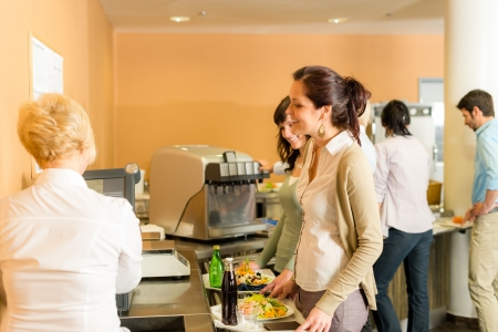 break fast: Cafeteria woman pay at cashier hold serving tray fresh food Stock Photo