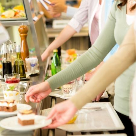 Postres a la gente con la cafetería comedor de la bandeja para servir de auto servicio Foto de archivo