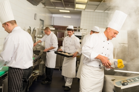 Professional kitchen busy team cooks and chef prepare meal