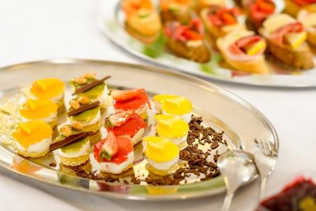 postres: Aperitivos de mini postres en buffet de comidas mantel blanco