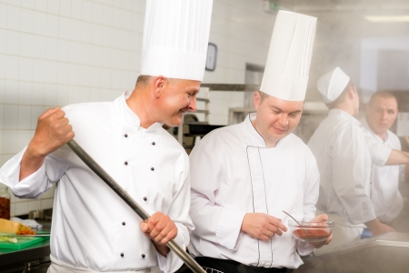 Two male cooks working in professional industrial kitchen prepare food photo