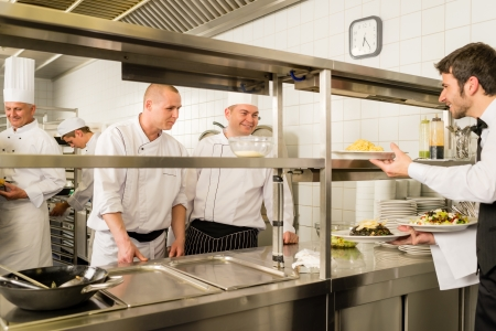canteen: Restaurant waiter take meals from professional cook stainless kitchen