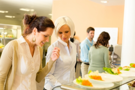 Lunch break business woman select meal from display cabinet canteen photo