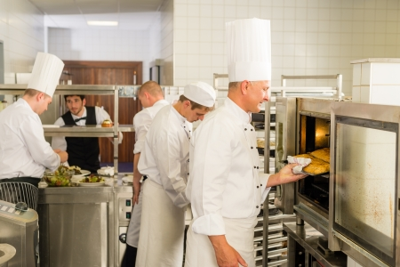 busy restaurant: Group of cooks in professional kitchen prepare meals restaurant service