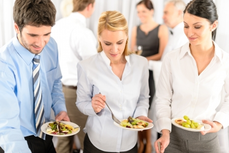 Business colleagues serve themselves at buffet catering service company event Imagens