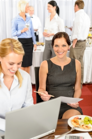 Business woman work computer during company lunch buffet