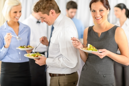 lunch meeting: Smiling business woman during company lunch buffet hold salad plate Stock Photo