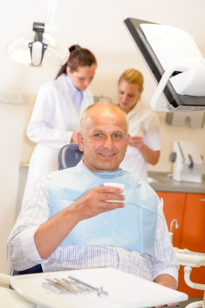 Mature man being treated at dental surgery smiling photo