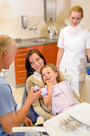 Little girl visit dentist surgery show teeth to stomatology specialist photo
