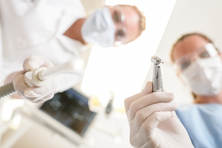 dental nurse: Female dentist focus on drill from  patient point of view