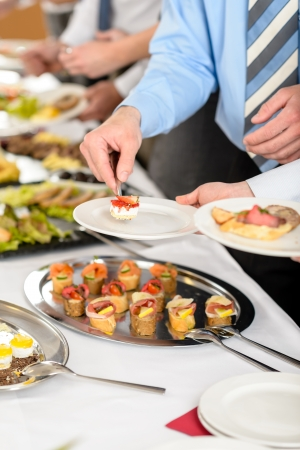 Catering at business company event people choosing buffet food appetizers photo