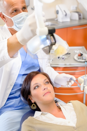 Woman patient at dental surgery with male hygienist stomatology clinic photo