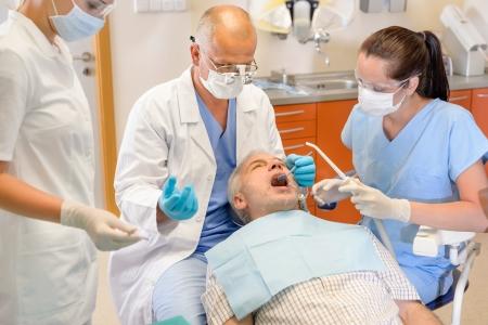 Hombre mayor en la cirug�a dental dentista que tiene la operaci�n Cl�nica Estomatol�gica photo