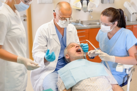 Senior man at dentist surgery having tooth operation stomatology clinic photo
